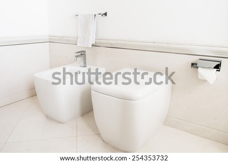 Toilet and bidet in a modern bathroom - lid closed - stock photo