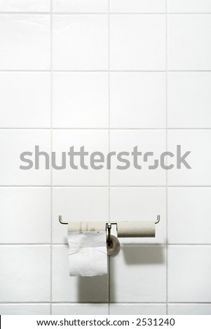 toilet paper holder with two rolls, only one sheet left - stock photo