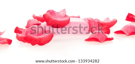 Toilet soap under petals of the roses, isolated on white. - stock photo