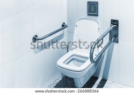 toilet with handrails for the disabled. Focus on the lid of the toilet. space left for your text - stock photo