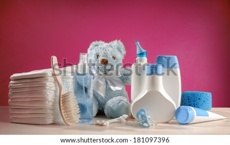 toiletries baby with diapers and pacifiers, and pink background - stock photo