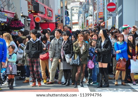 TOKYO - APRIL 1 2012: People, mostly youngsters, walk through Takeshita Dori near Harajuku train station on Sunday April 1 2012. Takeshita Dori is considered a birthplace of Japan's fashion trends. - stock photo