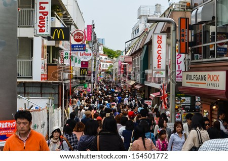 TOKYO - APRIL 29 2013: People, mostly youngsters, walk through Takeshita Dori near Harajuku train station on Sunday April 29 2013. Takeshita Dori is considered a birthplace of Japan's fashion trends. - stock photo