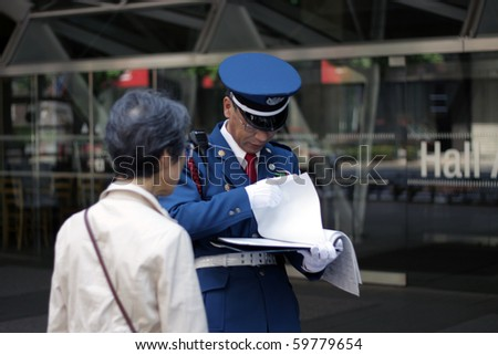 TOKYO - AUGUST 13: Japanese policeman explains directions to an elderly lady in central  on August 13, 2010 in Tokyo. - stock photo