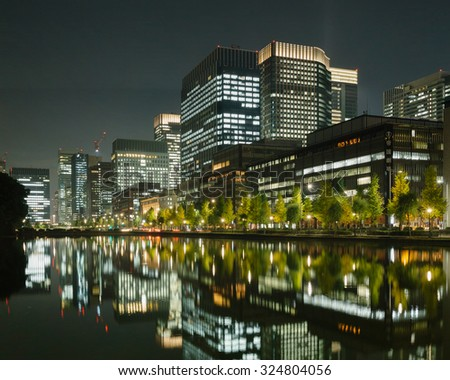 Tokyo business district with tall office buildings and the imperial palace moat at night - stock photo