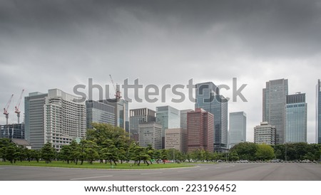 Tokyo City Skyscraper, with glass windows reflecting the surrounding buildings. - stock photo