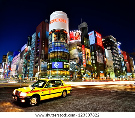 TOKYO - DECEMBER 25, 2012: A Taxi at Ginza District December 25, 2012 in Tokyo, JP. Ginza extends for 2.4 km and is one of the world's best known shopping districts. - stock photo