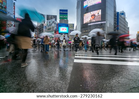 TOKYO - FEB 18: Pedestrians cross at Shibuya Crossing on Febuary 18, 2015 in Tokyo, Japan. The crosswalk is one of the world's most famous implementations of a scramble crosswalk. - stock photo