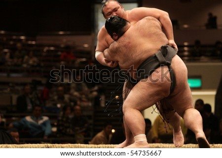 TOKYO - FEBRUARY 01: Two sumo wrestlers in a tight grip during the Tokyo Grand Sumo Tournament, February 01, 2010 in Tokyo, Japan. - stock photo