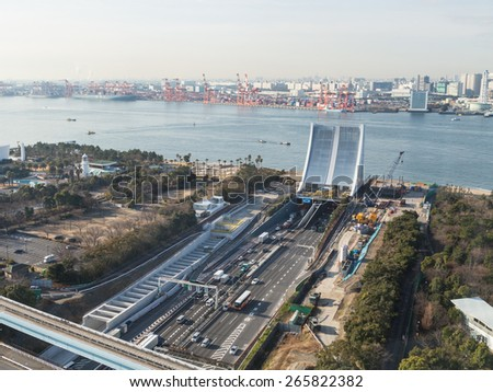 Tokyo - February 4, 2015: Urban Tokyo in Odaiba area with a modern highway passing under the river and see the entrance to the underwater tunnel February 4, 2015, Tokyo, Japan