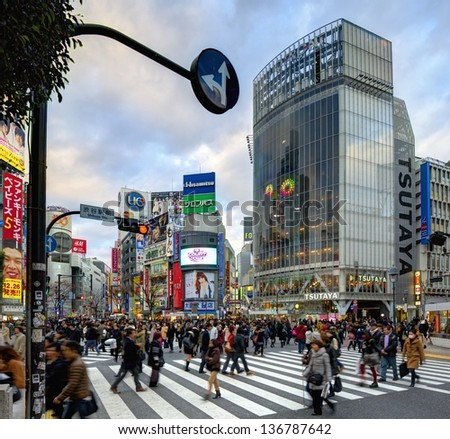 TOKYO - JANUARY 10: Pedestrians at Shibuya crossing January 10, 2013 in Tokyo, JP. The famed crossing is one of the most well known examples of a scramble crosswalk. - stock photo