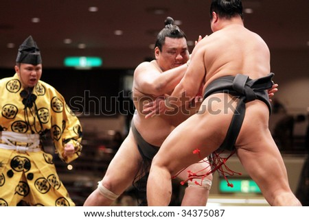 TOKYO - JANUARY 21: Two sumo wrestlers engaged in a fight at the Tokyo Grand Sumo Tournament, January 21, 2009 in Tokyo, Japan. - stock photo