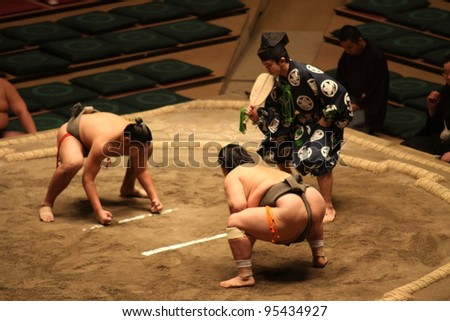 TOKYO - JANUARY 14: Unidentified wrestlers in the Grand Sumo Tournament in Tokyo, Japan on January 14, 2012. Although baseball has surpassed sumo in viewers, it is still Japan's national sport - stock photo