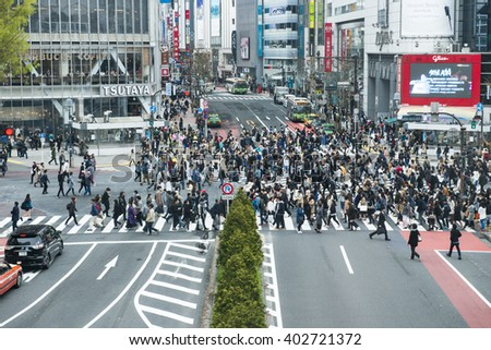TOKYO, JAPAN - APRIL 02, 2016: Pedestrians walk at Shibuya Crossing during the holiday season. The scramble crosswalk is one of the largest in the world. - stock photo
