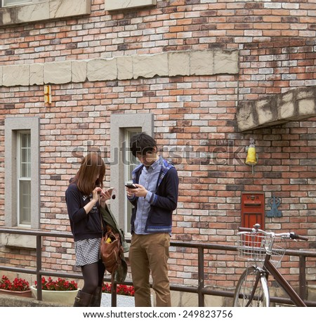 TOKYO, JAPAN - APRIL 19 : Young couple using mobile device on Cat street, Harajuku taken April 19, 2014 in Tokyo. Cat street is popular among young people in Harajuku district. - stock photo