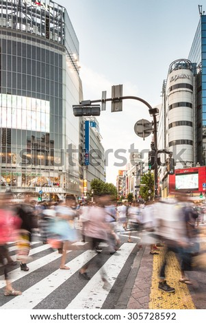 Tokyo, Japan - August 18 2013: A large crowd captured with blurred motion walk through the world famous Shibuya crossing in Tokyo. - stock photo