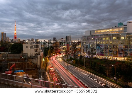Tokyo, Japan - Dec 11, 2015: Dusk over Tokyo with stormy sky at Roppongi District. The iconic Tokyo Tower is visible at the distance. - stock photo
