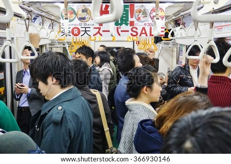 TOKYO, JAPAN -4 DECEMBER 2015- Commuters are packed inside a car in the Tokyo metro subway. The greater Tokyo metropolitan area has an extensive public transit system. - stock photo