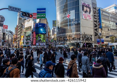 TOKYO, JAPAN - February 16, 2016: Crowd people walk at Shibuya Crossing during the holiday season. The scramble crosswalk is one of the largest in the world.