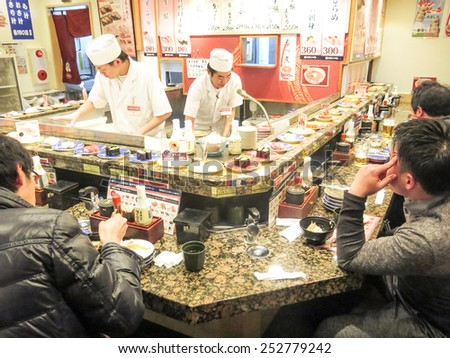 TOKYO,JAPAN - FEBRUARY 11,2015: people eating in a Sushi restaurant in Tokyo.Sushi is a traditional japanese specialty known all over the world. - stock photo