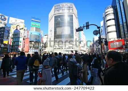 TOKYO, JAPAN - JANUARY 10,2015 : Pedestrians walk at Shibuya Crossing during the holiday season. The scramble crosswalk is one of the largest in the world. - stock photo