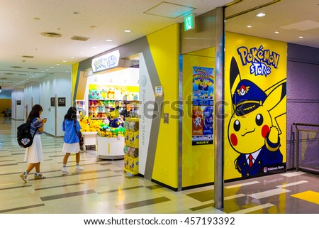TOKYO, JAPAN - JULY 21, 2016: Pikachu stuffed dolls greet young Asian girls walking into the Narita Airport Pokemon Store entrance. Vertical