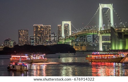 TOKYO, JAPAN - JULY 12TH, 2017. Dinner boat cruise, locally known as yakatabune at Odaiba waterfront with Tokyo's Rainbow bride on the background.