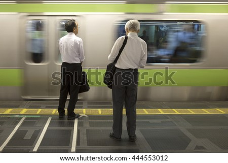 TOKYO-JAPAN, 27 June 2016:  Business people waiting for the JR train and fast moving train. It is one of Tokyo's busiest and most important lines in Tokyo, Japan. - stock photo