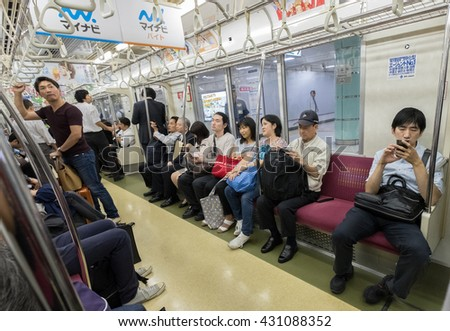 TOKYO, JAPAN - JUNE 2ND 2016. Commuters at Tokyo Metro subway. Tokyo Metro subway is a popular mode of transportation in Tokyo for people to commute.  - stock photo