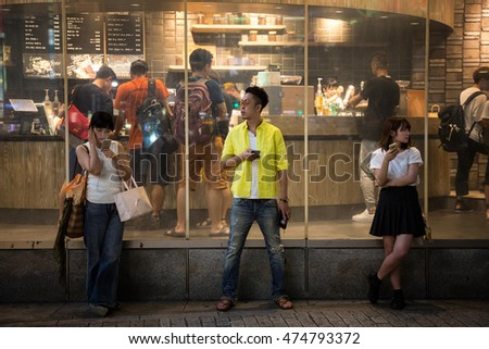TOKYO, JAPAN - 26 JUNE 2016 - Young people with their mobile phones, outside Starbucks at Shibuya Crossing, Tokyo, Japan.