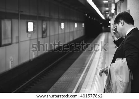 TOKYO JAPAN 7 MAR 2016 :A tired asian businessman , strain at train station , tokyo japan, b/w filter - stock photo