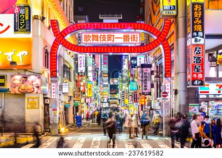 TOKYO, JAPAN - MARCH 14, 2014: Pedestrians walk below signs densely lining an alleyway in Kabuki-cho. The area is a renown nightlife and red-light district. - stock photo