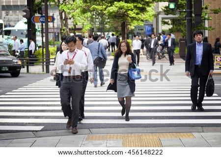 TOKYO, JAPAN - MAY 19: Businessmen during lunch break in business district Nishi-Shinjuku on May 19, 2016 in Tokyo, Japan. - stock photo