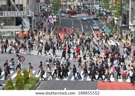 TOKYO, JAPAN - MAY 11, 2012: Commuters hurry in Shibuya, Tokyo. Shibuya crossing is one of busiest places in Tokyo and is recognized thanks to being featured in multiple films. - stock photo
