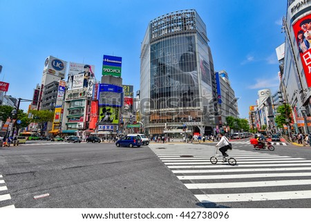 TOKYO, JAPAN - MAY 23, 2016: Pedestrians walk at Shibuya Crossing. The crossing is one of the world's most famous examples of a Scramble Crosswalk. - stock photo