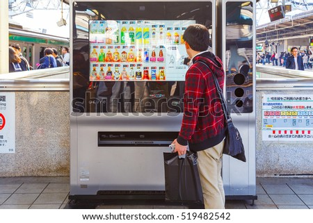 TOKYO, JAPAN - NOVEMBER 29 2015: An unidentified Japanese buy a drink from an automatic vending machine at ikebukuro station
