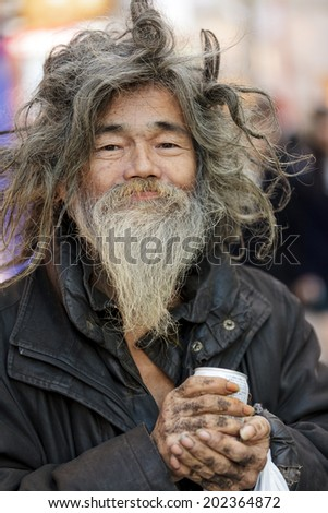 TOKYO,JAPAN, November 25 : Cheerful tramp  holding a drink can, posing in the street near the Shibuya crossroad in Tokyo, Japan, on November 25, 2011 - stock photo