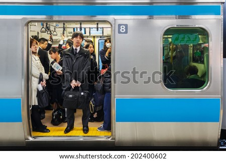 TOKYO, JAPAN - NOVEMBER 26: Train Commuters in Tokyo, Japan on November 26, 2013. Tokyo train is always packed with people all through the day and especially in rush hours - stock photo