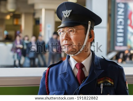 TOKYO, JAPAN - NOVEMBER 23: Train Conductor in Tokyo, Japan on November 23, 2013. Unidentified Japanese train conductor observes passenger before train arrives at the platform