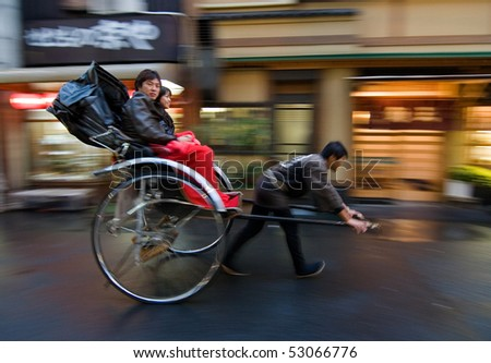 TOKYO, JAPAN - NOVEMBER 10:  Two people on a rickshaw being pulled on the street November 10, 2007 in Asakusa, Tokyo, Japan. - stock photo
