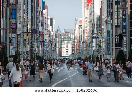 TOKYO, JAPAN - SEPTEMBER 22: Shoppers and tourists wander the shops and streets of  Ginza on September 22, 2013 in Tokyo, Japan. - stock photo