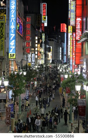 TOKYO - JUNE 13: People walk through light up streets with neon signs on June 13, 2010 in Tokyo. - stock photo