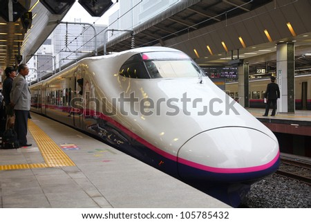 TOKYO - MAY 4: Travelers board Shinkansen Hayate train on May 4, 2012 at Tokyo Station. Hayate has top operating speed of 275km/h and is among fastest trains worldwide. - stock photo