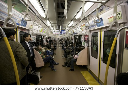TOKYO- NOVEMBER 17: Rush hour commuters riding the Tokyo metro transit system in Tokyo, Japan on November 17, 2009.  The transit system carries almost an average of 8 million passengers daily. - stock photo