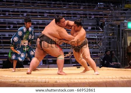 TOKYO - NOVEMBER 18: Senior sumo wrestler fighting a smaller opponent in the Fukuoka Tournament on November 18, 2010 in Fukuoka, Japan. - stock photo