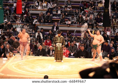 TOKYO - NOVEMBER 18: Sumo wrestlers perform the salt throwing tradition before a fight in the Fukuoka Tournament on November 18, 2010 in Fukuoka, Japan. - stock photo
