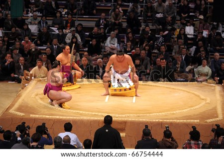 TOKYO - NOVEMBER 18: The three highest ranking sumo wrestlers performing a traditional ritual in the Fukuoka Tournament on November 18, 2010 in Fukuoka, Japan. - stock photo
