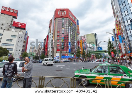 TOKYO-Sept 20, 2009: The famous Akihabara Electric Town is known as a shopping district for video games, anime, manga, computer and tech electronics. Two men and a taxi in the foreground.