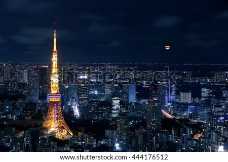Tokyo tower and the night view of Tokyo city, Japan with a full moon covered by clouds