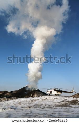 TOLBACHIK VOLCANO, KAMCHATKA, RUSSIA - FEBRUARY 2, 2013: Eruption Tolbachik Volcano, helicopter and tourists near dangerous smoking volcano on a sunny day. Russia, Far East, Kamchatka Peninsula. - stock photo